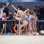 юная гимнастка в прыжке на соревнованиях